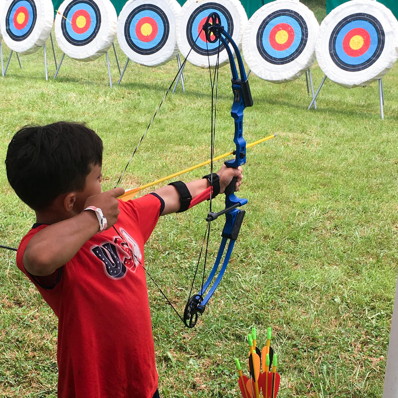 A boy wih a bow and arrow preparing to loose the arrow at a target