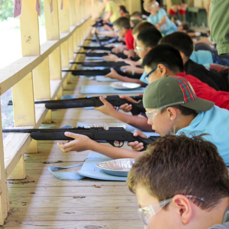 A group of scouts shooting BB guns on the firing line of a rifle range