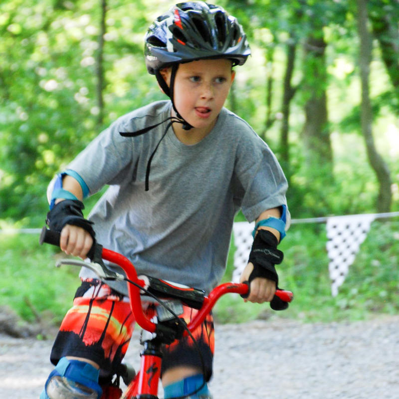 A boy peddles a BMX bike around a track with checkered flags in the background