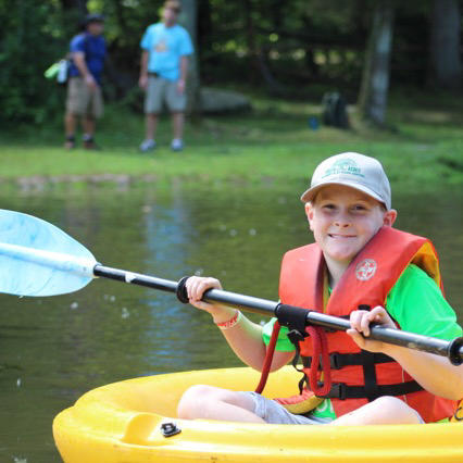 A young scout smiles with a paddle in a small personal boat