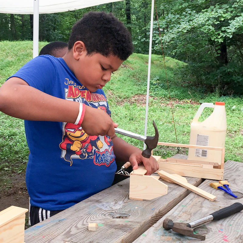 A boy hammers a nail into the wooden toolbox he is building