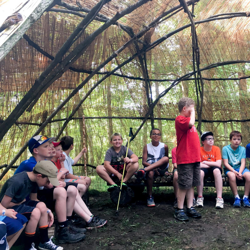 A dozen scouts gathered around inside of a wigwam made from natural materials