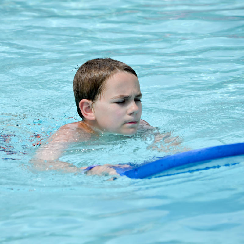 A young boy swims with a kickboard