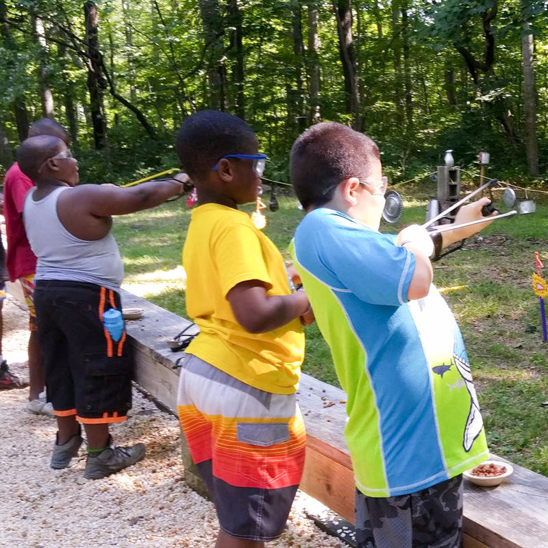 Four young scouts shooting slingshots