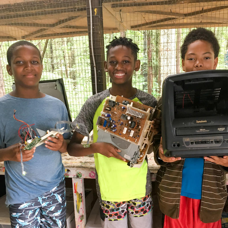 Three boys hold up parts of a small disassembled television