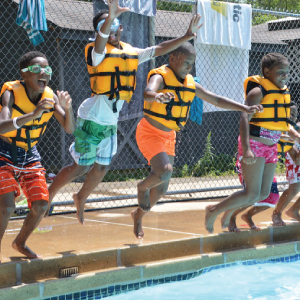 A small group of young campers in life preservers jumping into a pool